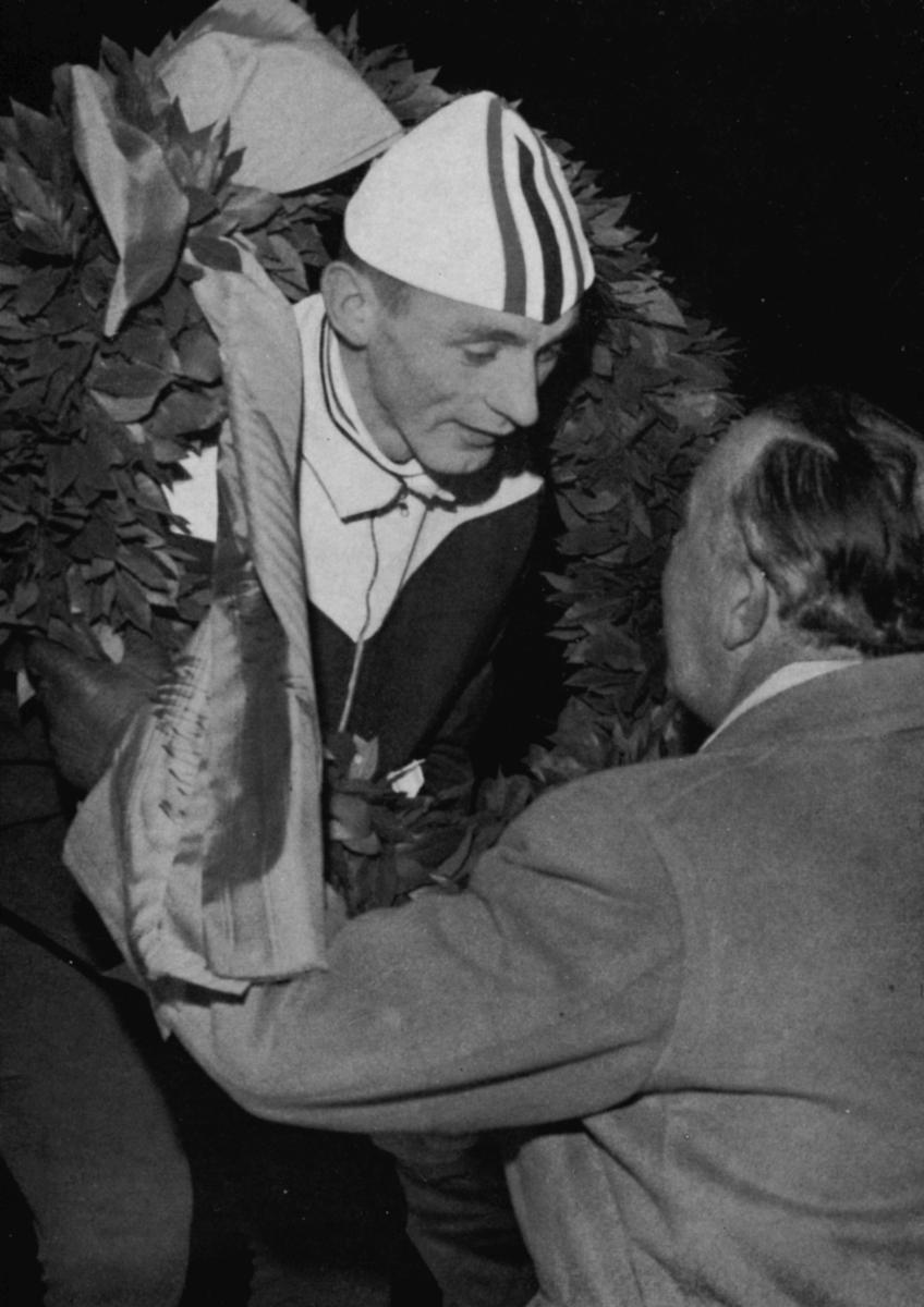 Bilde av skøyteløperen Nils Aaness laubærkransen av Sveriges prins Bertil.