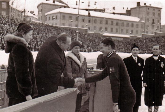 Bilde av skøyteløperen Finn Helgesen, som gratuleres med OL-gull av kronprins Olav.