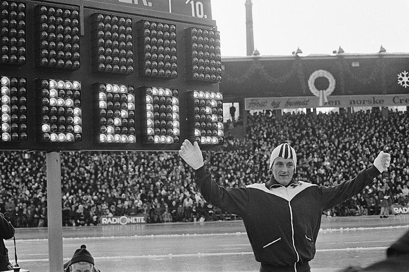 Bilde av skøyteløperen Fred Anton Maier foran lystavla som viser ny verdensrekord på 10.000 m - 15.20.3.